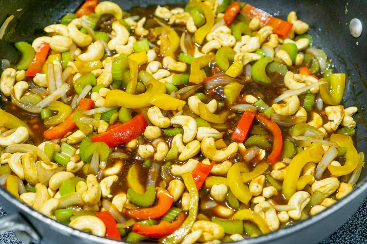 cashews, bell peppers, celery in a pineapple stir fry sauce in a pan