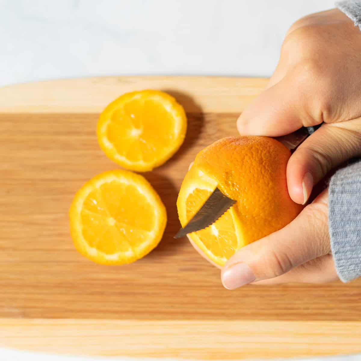 using a knife to peel an orange