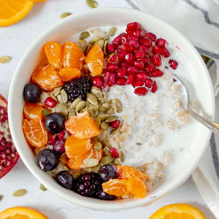 bowl of vegan oatmeal with pomegranate oranges, berries