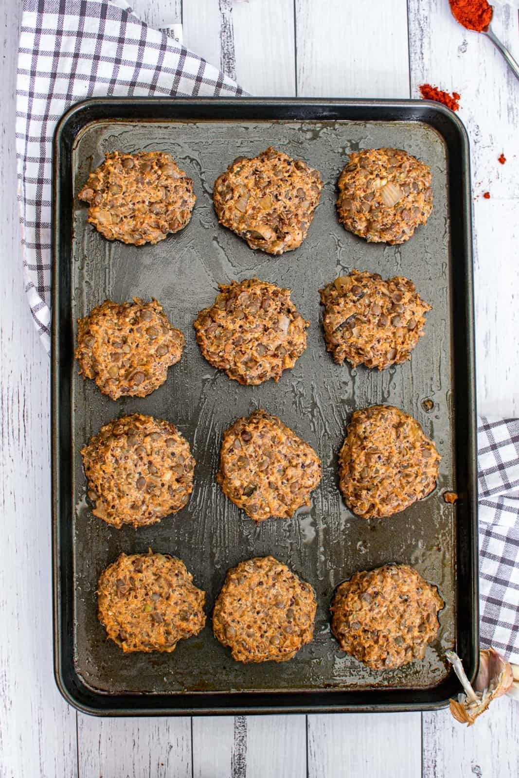 vegan lentil cakes on a baking sheet, ready to be cooked
