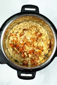 Mixing cooked spaghetti in the Instant Pot with baked feta.