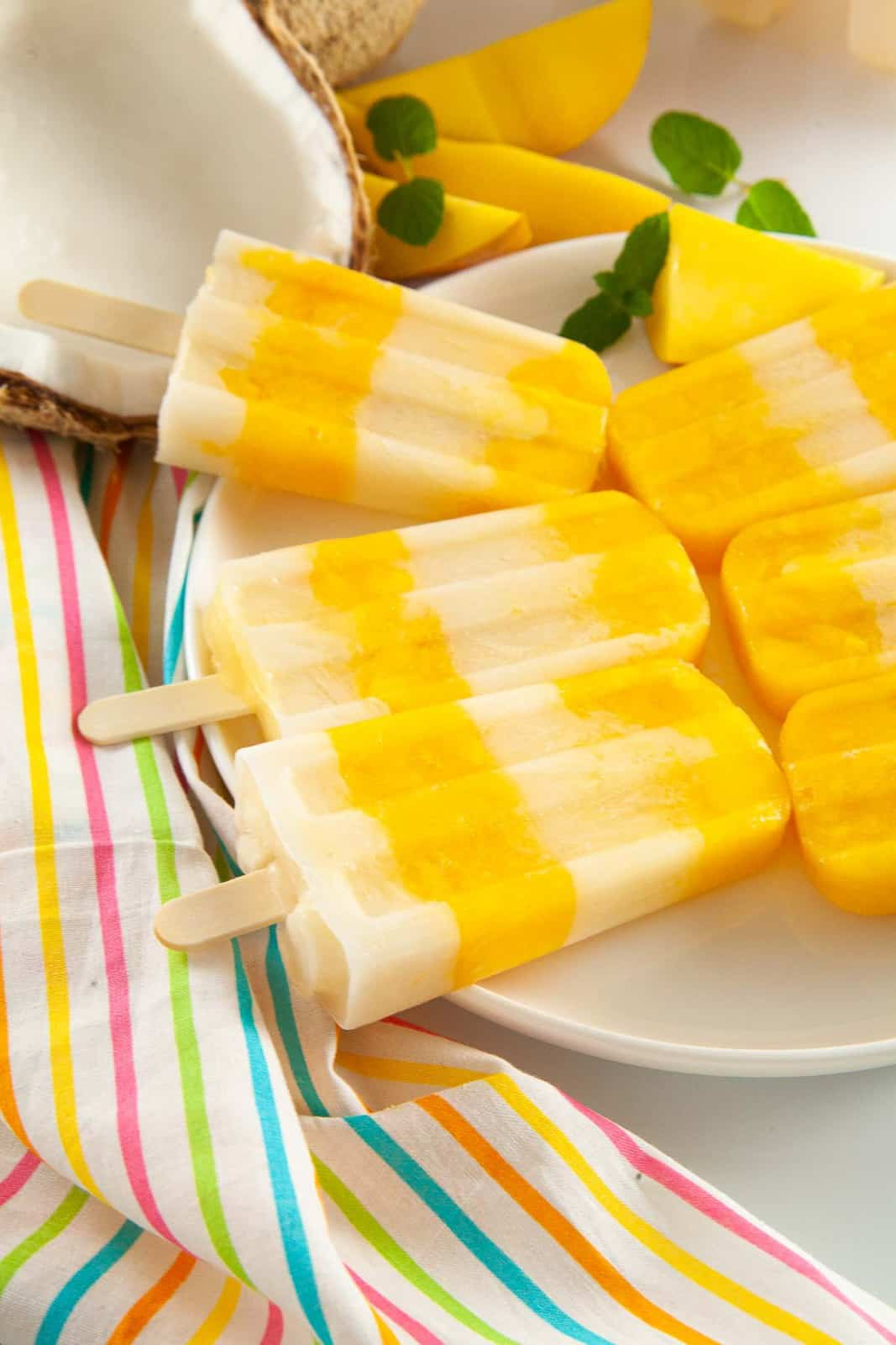 Layered mango popsicles with coconut milk on a plate.