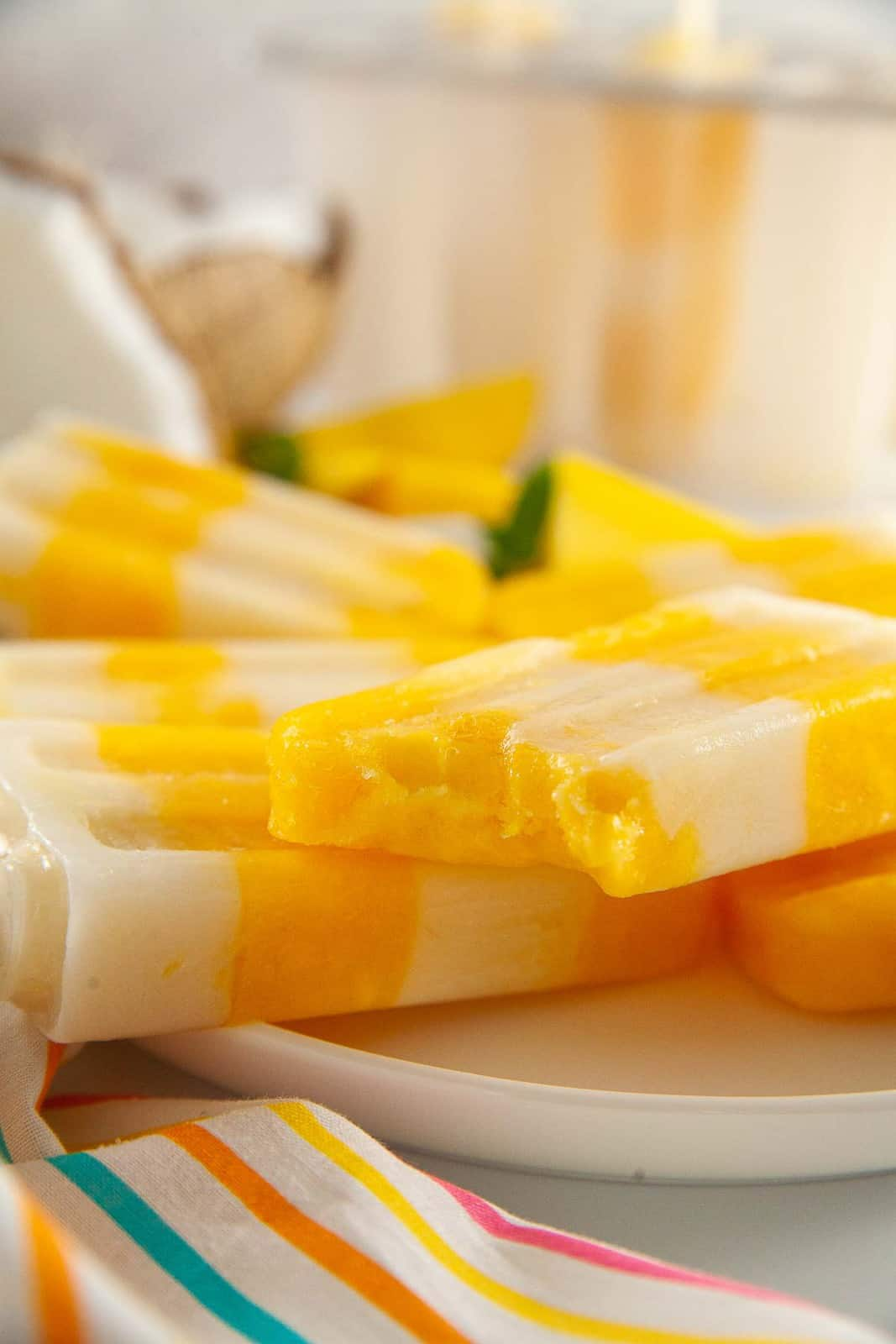Vegan mango popsicles with a bite taken out of one.