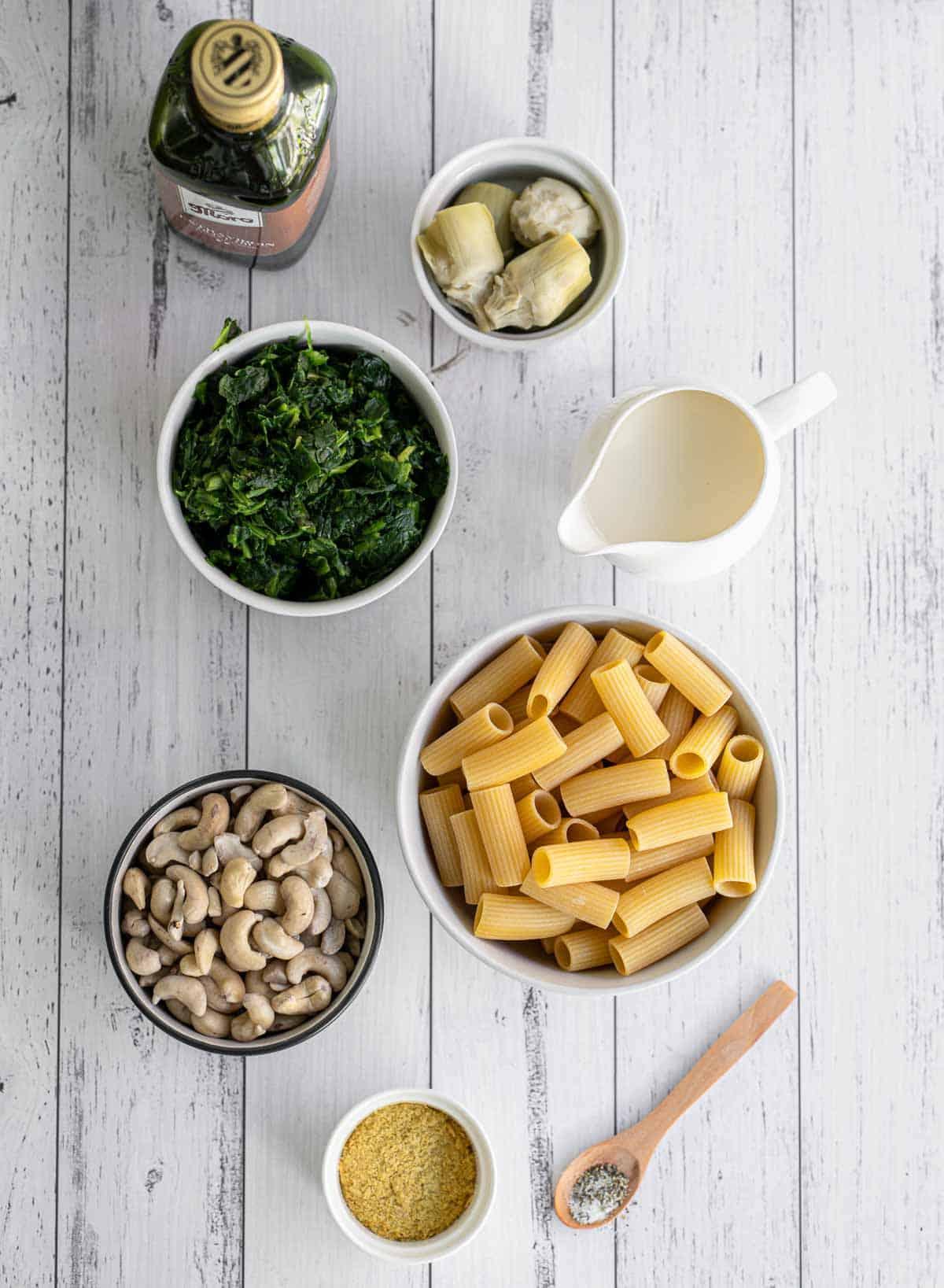 Ingredients to make creamy spinach artichoke pasta.