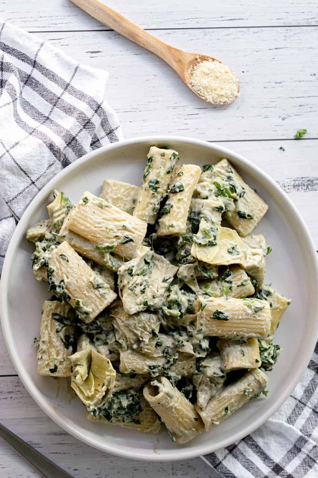 Plate of vegan spinach artichoke creamy pasta.
