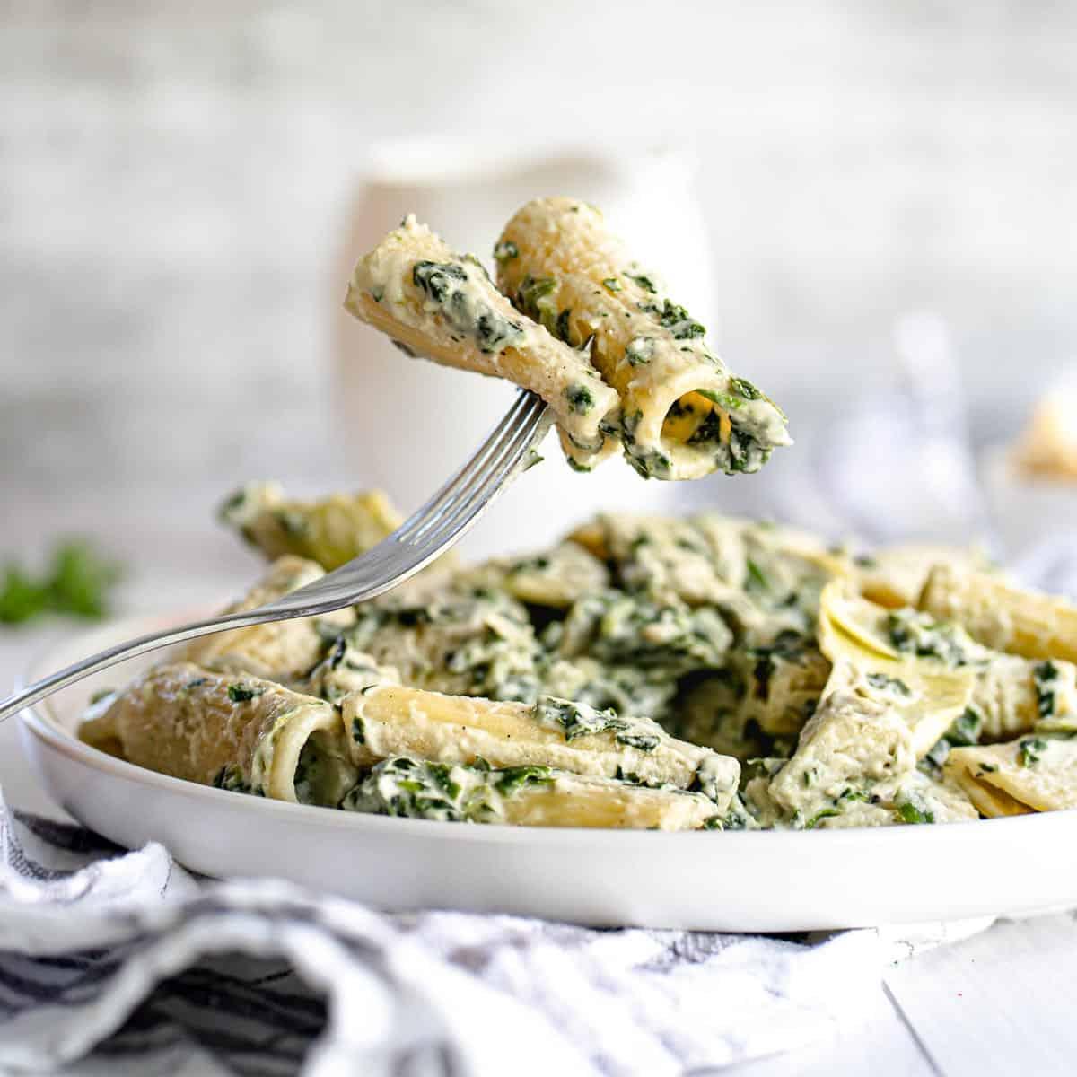Fork holding rigatoni with spinach artichoke Alfredo sauce.