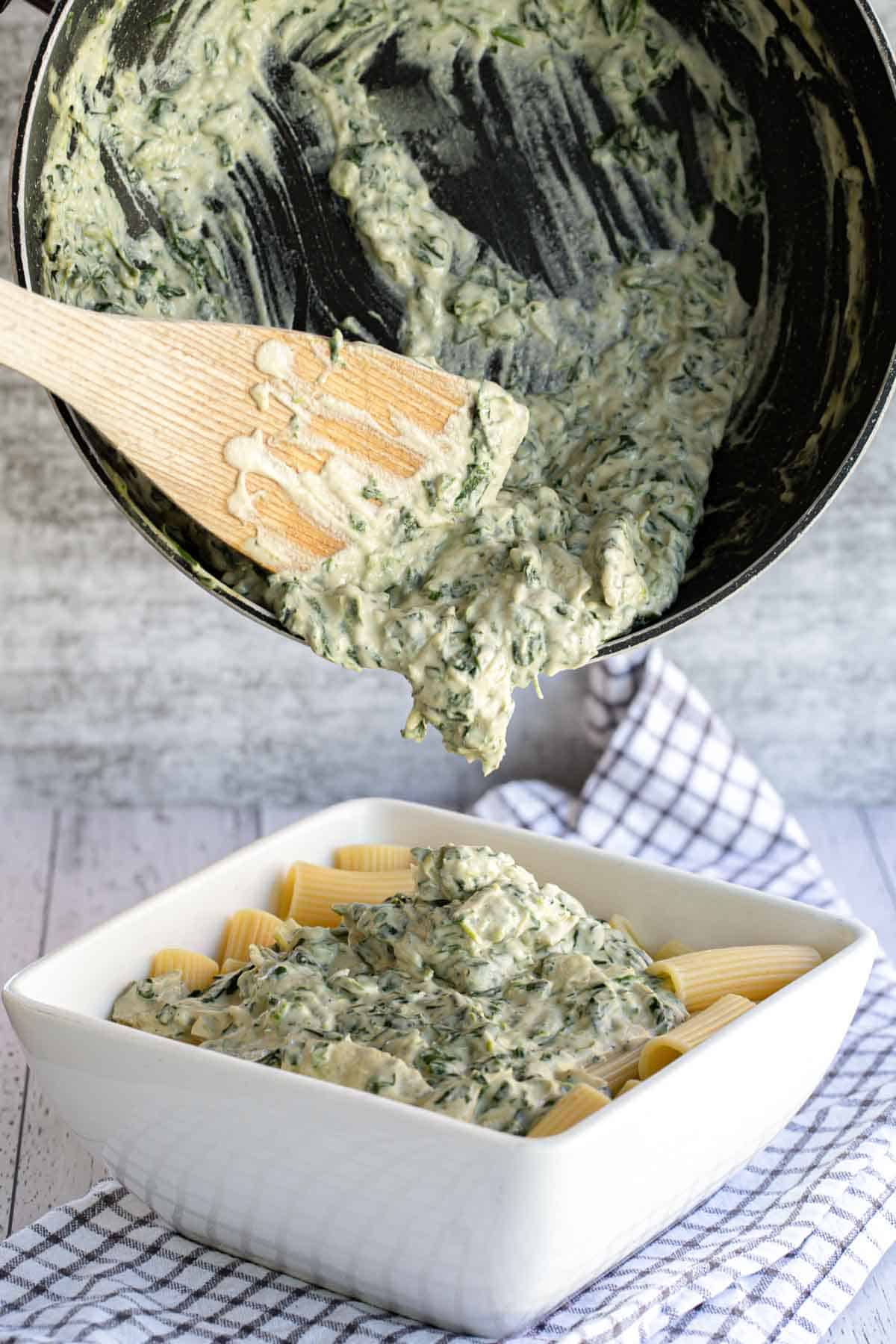 Pouring spinach artichoke sauce over pasta.