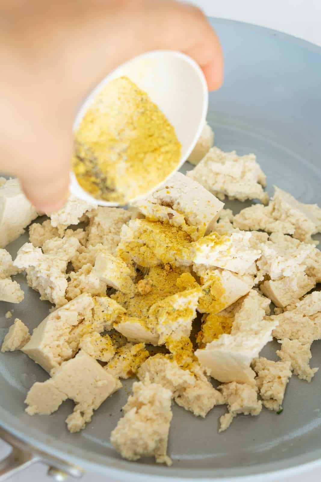 Adding seasonings to tofu to make tofu scramble.