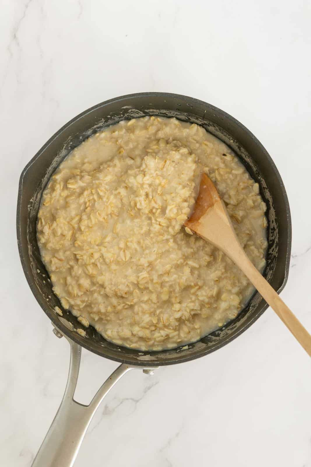 Cooking savory oatmeal in a saucepan.
