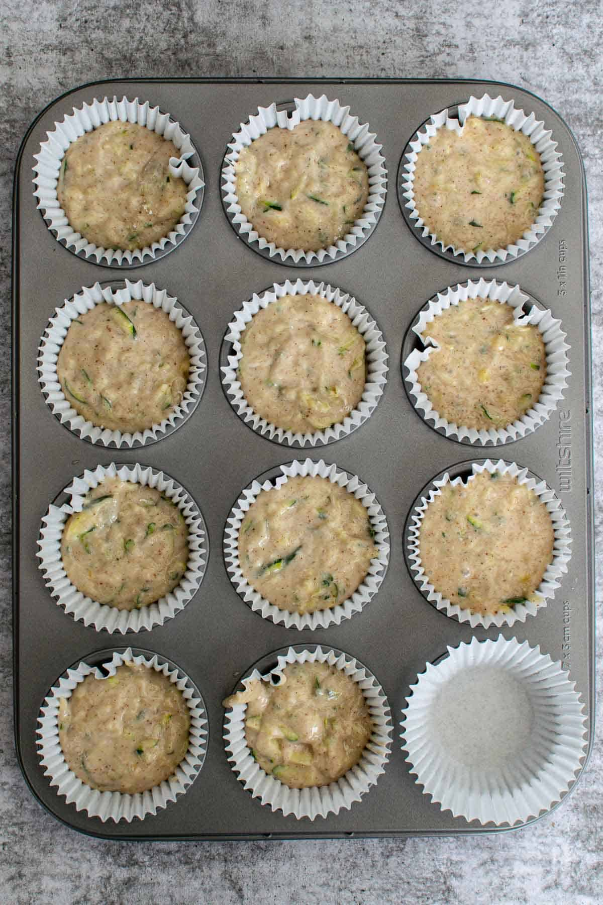 Gluten free zucchini muffin batter in a muffin pan ready to bake.