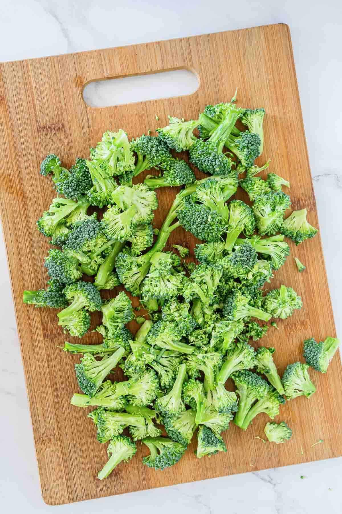 Cutting broccoli florets on a cutting board.