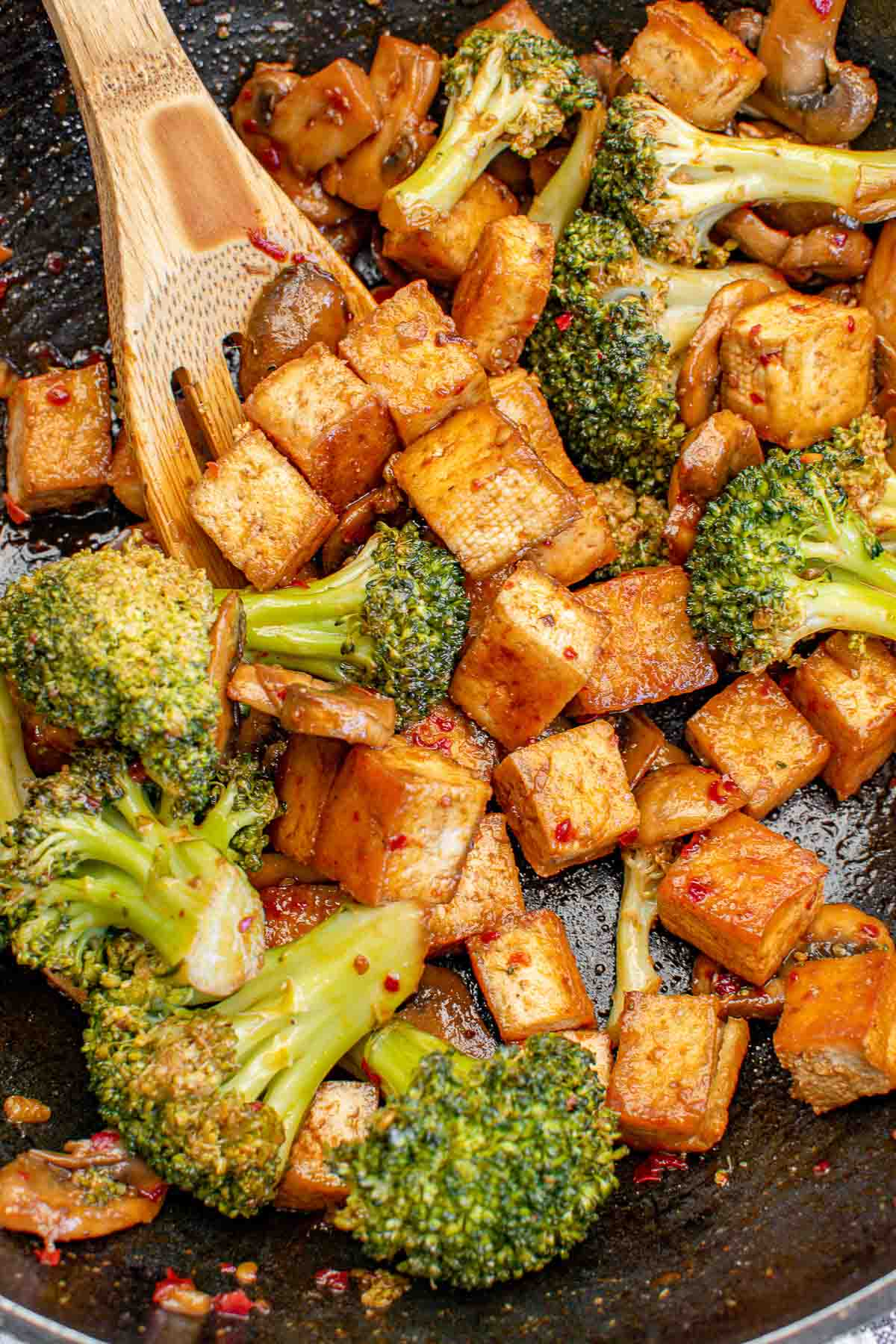 Broccoli and cubed fried tofu in a wok.