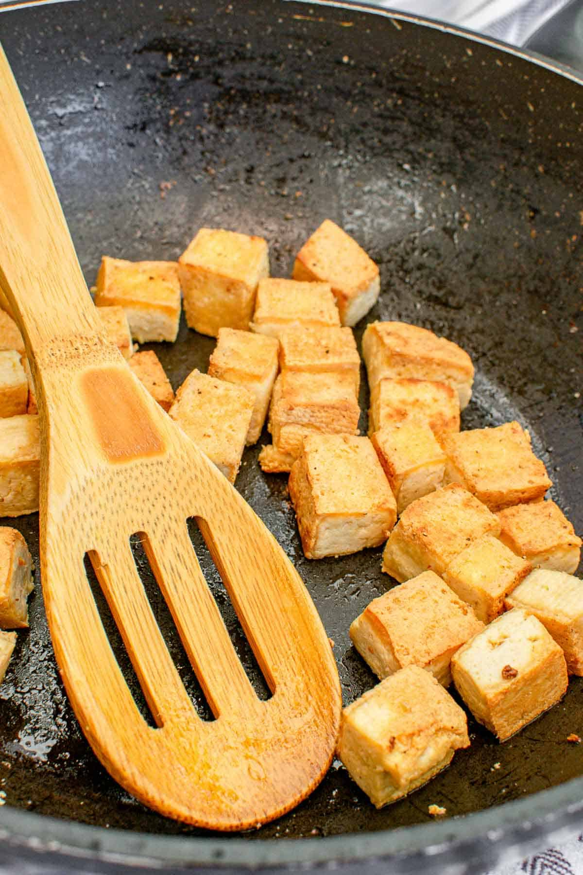 Frying tofu cubes until crispy.