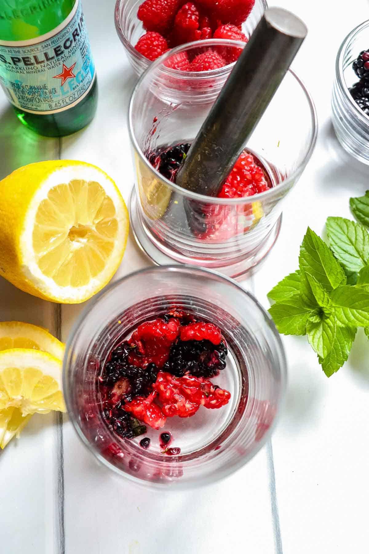 Muddling raspberries and blackberries in a glass.