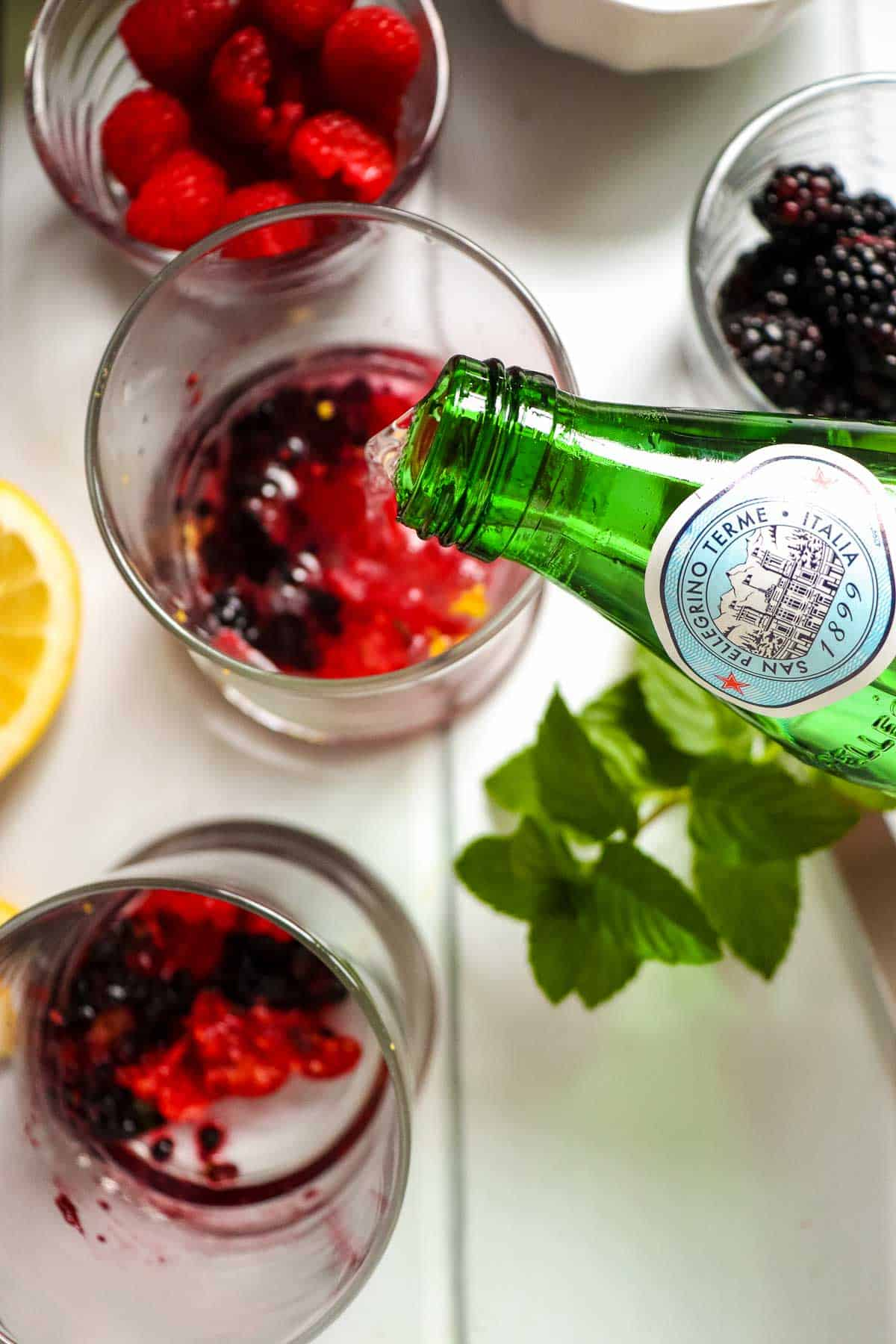 Adding sparkling water to a glass.