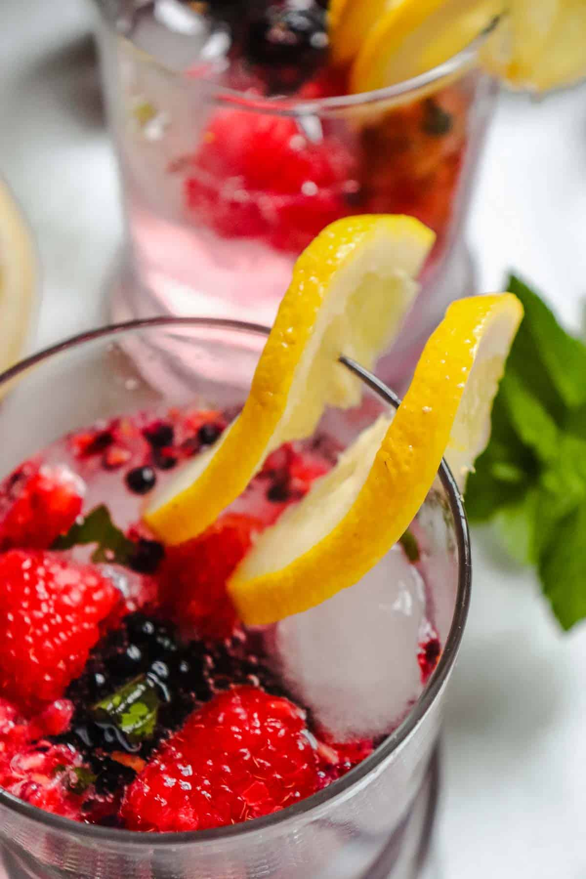 Glass of berry spritzer garnished with lemon slices.