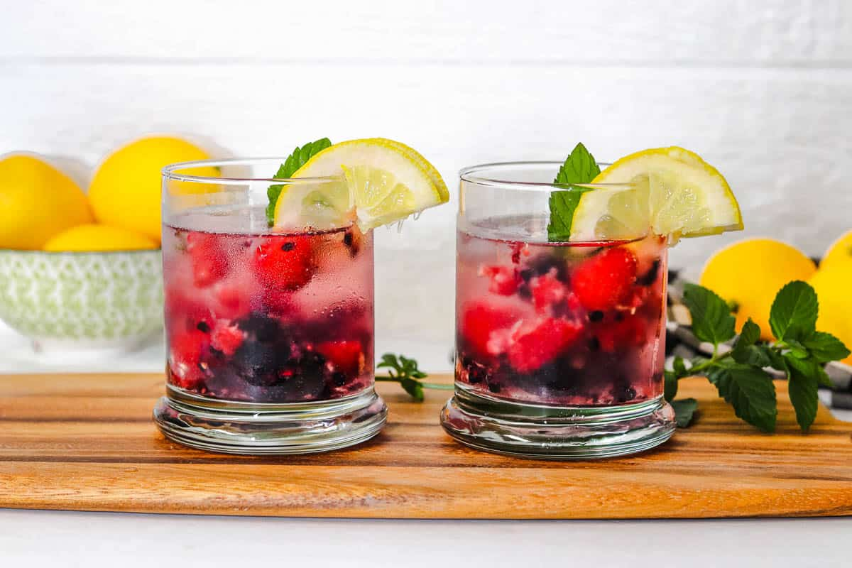 Two glasses of blackberry and raspberry spritzers.