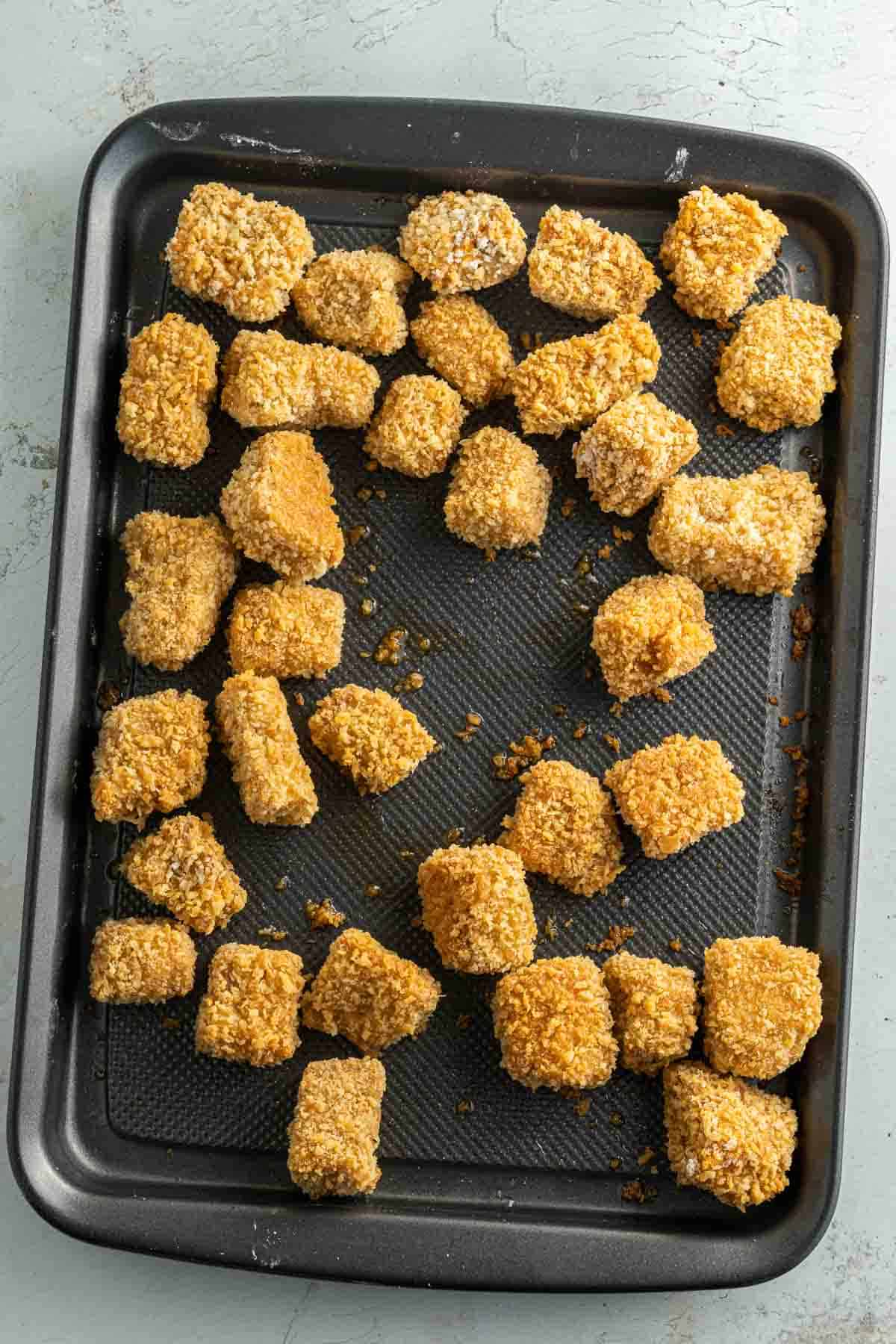 Baked tofu nuggets on a baking pan.