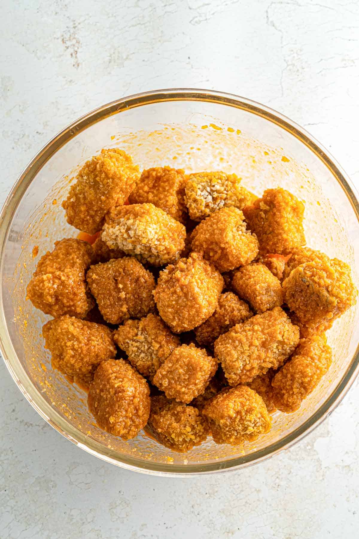 Bowl of crispy baked tofu nuggets tossed with buffalo sauce.