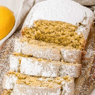 Close up of lemon loaf sliced on a cutting board.
